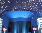 Mitzvah setup with ceiling star effect, up lighting, and twin TVs