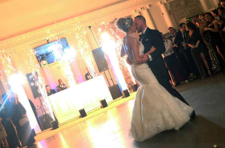Bride and groom kiss while indoor fireworks set off